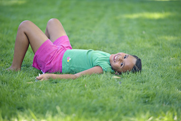 Young African girl laying in grass smiling