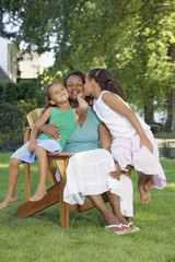 African mother and young daughters hugging outdoors