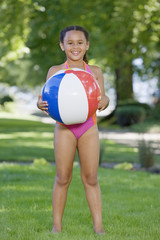 Young African girl wearing bathing suit and holding ball outdoors