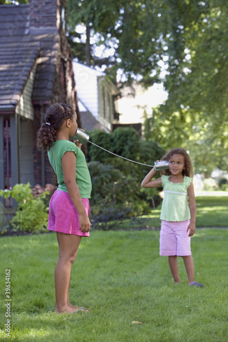 Young African sisters playing telephone with two cans on the end of string outdoors