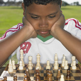 African boy looking at chess board outdoors