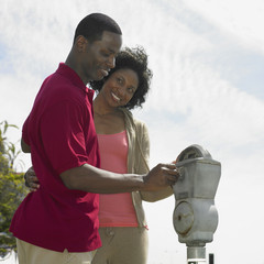 African couple putting coins in parking meter