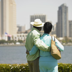 Senior couple looking at cityscape across water