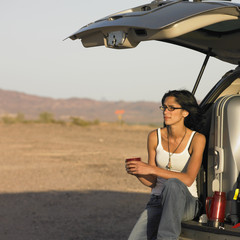 Hispanic woman in deserted area sitting on tailgate of truck