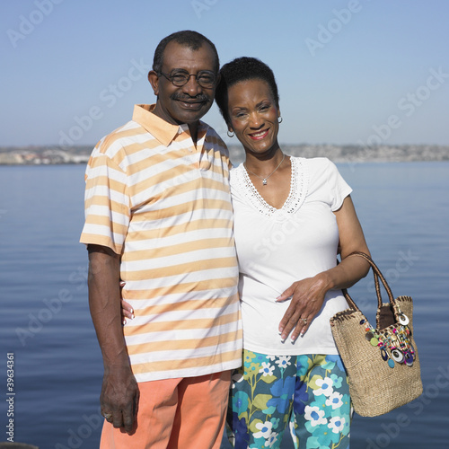 Senior African couple hugging next to water