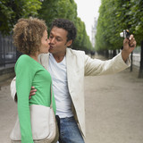 African couple taking own photograph in park