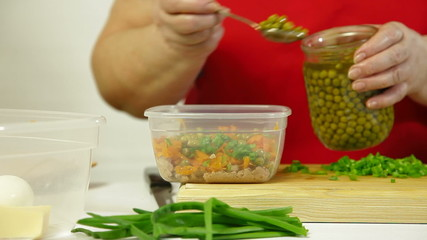 Mature woman adds canned green pea to the cod-liver salad