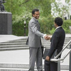 Two businessmen shaking hands on stairs outdoors