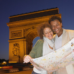 Couple looking at map in Paris at night