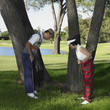Senior Asian couple looking at bad lie on golf course