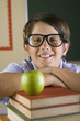 Hispanic boy with stack of books and apple in classroom