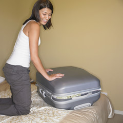 Asian woman trying to close suitcase