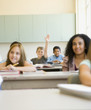 Students smiling at desks in classroom