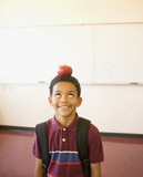 Boy with apple on head in classroom