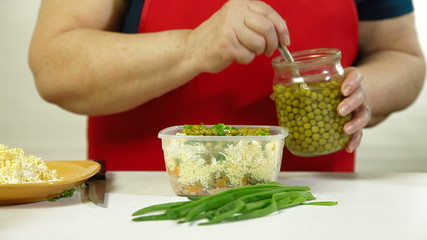 Mature woman cooking cod liver salad - adds canned green pea