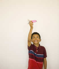 Studio shot of boy playing with toy missile