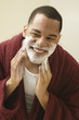 African man applying shaving cream to face