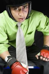 Bruised businessman wearing sparring gloves and helmet