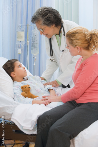 Senior female doctor talking to girl in hospital bed