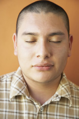 Studio shot of Hispanic teenaged boy with eyes closed