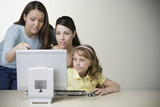 Hispanic mother and daughters working on computer