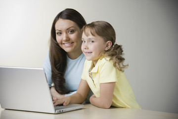 Hispanic sisters smiling with laptop