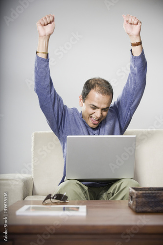 Indian man looking at laptop and cheering