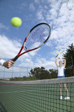 Woman hitting tennis ball through other players racket