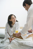 Hispanic man bringing breakfast to wife in bed
