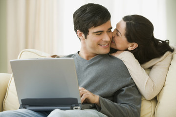 Hispanic couple hugging and using laptop