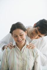 Hispanic man giving wife shoulder massage