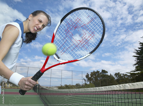 Hispanic woman holding tennis racket with hole in it