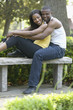 African couple hugging on bench