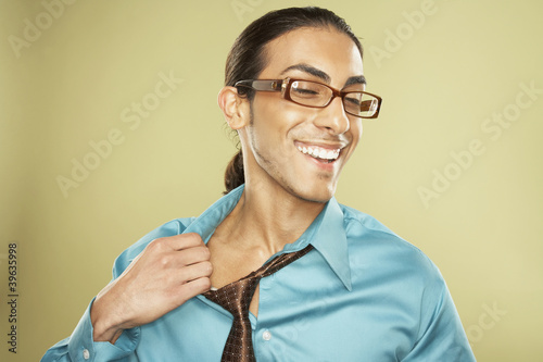 Middle Eastern businessman pulling off necktie
