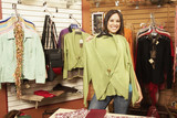 Hispanic woman holding up sweater in boutique
