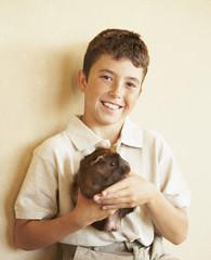 Hispanic boy holding guinea pig