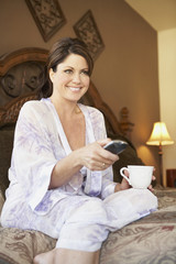 Woman holding coffee mug and watching television on bed