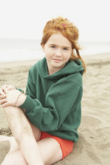 Girl with freckles sitting on beach