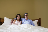 Middle-aged couple sitting in bed