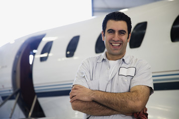 Repairman smiling in front of airplane