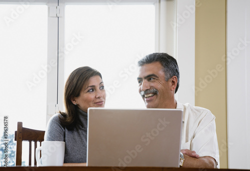 Middle-aged couple using laptop