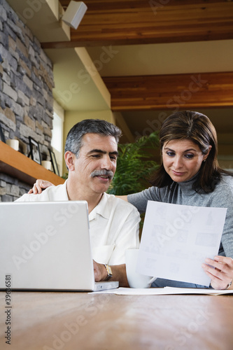 Middle-aged couple looking at paperwork and laptop