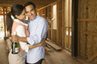 Hispanic couple hugging with champagne at construction site