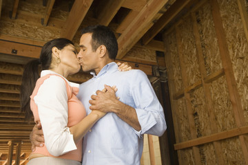 Hispanic couple kissing at construction site
