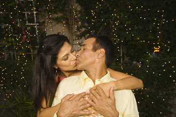 Hispanic couple kissing outdoors at night