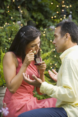 Hispanic woman appraising engagement ring in front of man