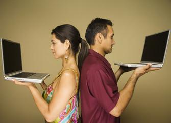 Hispanic couple standing back to back holding laptops