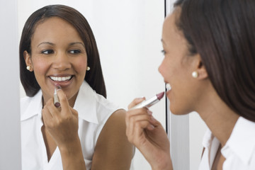 African woman applying lipstick in mirror