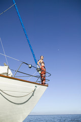 Asian woman standing on bow of sailboat