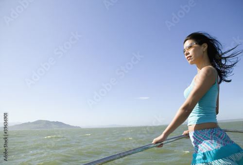 Asian woman leaning on rail of boat
